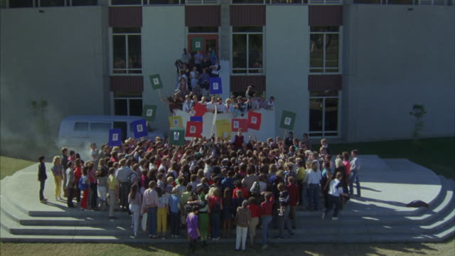 Students gather in protest in front of a building on a college campus.