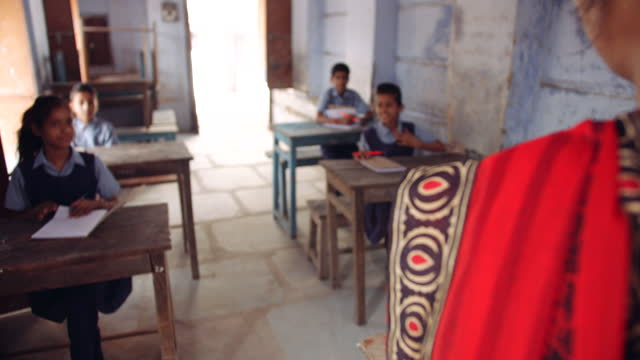 students gets up when a teacher enters the class room as they take seat and open their notebooks so that the class may start - india stock videos & royalty-free footage