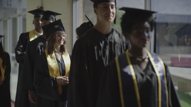 students graduating from high school waiting in a row in corridor / springville, utah, united states - springville utah stock videos & royalty-free footage