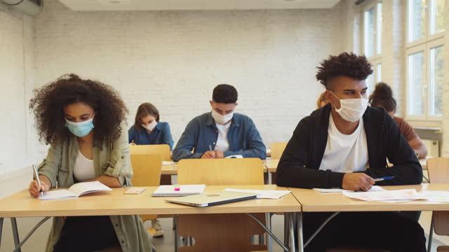studenten, die eine untersuchung während der coronavirus-pandemie haben - schulische prüfung stock-videos und b-roll-filmmaterial