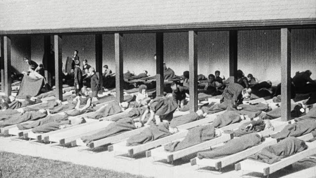 vídeos y material grabado en eventos de stock de 1925 montage students helping fellow students with blankets as they prepare to nap on cots in open-air pavilion, and students awakening / newcastle upon tyne, england, united kingdom - recostarse