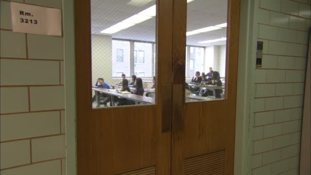 ms students in class with male teacher through door, brooklyn, new york city, usa - 高等学校点の映像素材/bロール