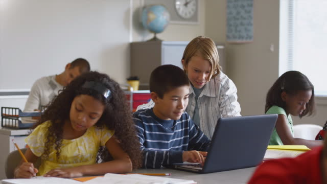 ms students (8-13) in classroom, one boy using laptop in classroom / edmonds, washington, usa - see other clips from this shoot 1750 stock videos and b-roll footage