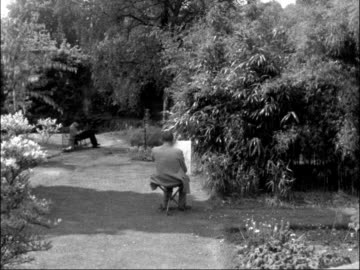 students in oxford enjoy hot weather; england: oxfordshire: oxford: ext traffic along oxford high street / students on bench in botanical gardens /... - high street stock-videos und b-roll-filmmaterial