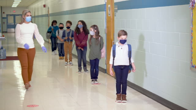 vídeos de stock e filmes b-roll de students in school hallway during covid-19 wearing masks - 6 7 years