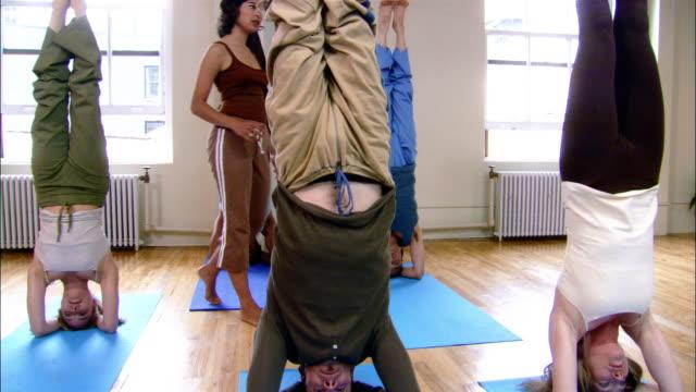 Students in sirsasana in yoga class