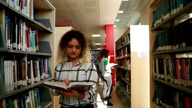 students in the library - libro di testo video stock e b–roll