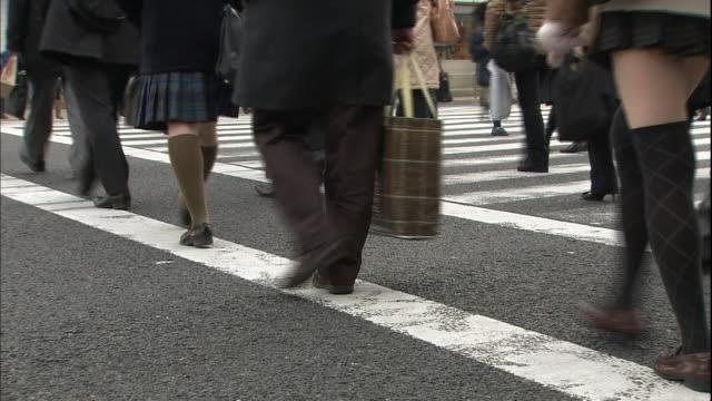 students in uniform walk with pedestrians on a city street crosswalk. - 制服点の映像素材/bロール