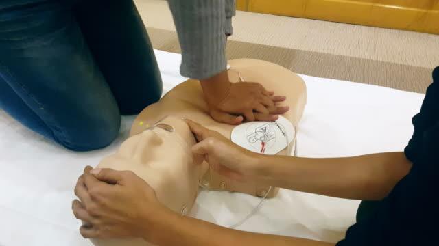 Studenter att lära sig att rädda patienterna i nödsituationer CPR utbildning klass med CPR docka och AED maskin