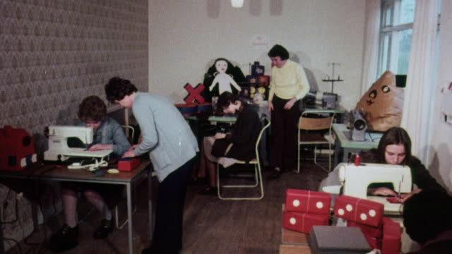 montage students learning how to sew and create toys used as teaching aids for handicapped and disabled children / united kingdom - 1976年点の映像素材/bロール