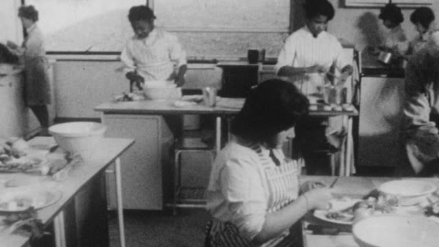 stockvideo's en b-roll-footage met 1962 montage students learning in a domestic science class at holland park school / kensington, london, england - home economics