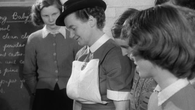 1952 montage students learning to care for a baby, bathing and caring for a doll while district nurse observes, headmaster calling on district nurse and alerting her to a patient in labor / wadhurst, england, united kingdom - wadhurst stock videos & royalty-free footage