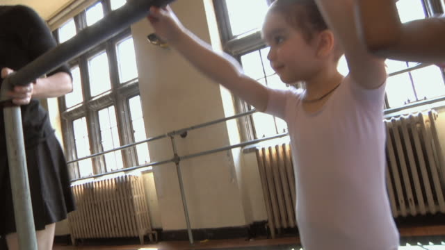 ms pan slo mo students (2-7) line up at barre to working on their form during their ballet class / chicago, illinois, usa - ballettstange stock-videos und b-roll-filmmaterial