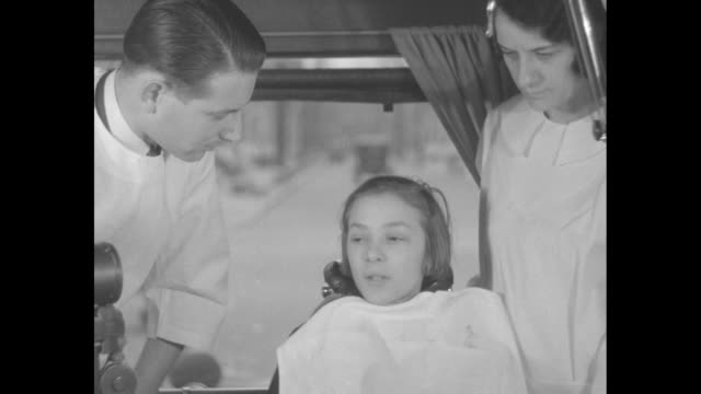 students lined up holding their cheeks walking towards bus / female students sitting in dental chair in bus, dentist and dental assistant on either... - dentist stock videos & royalty-free footage