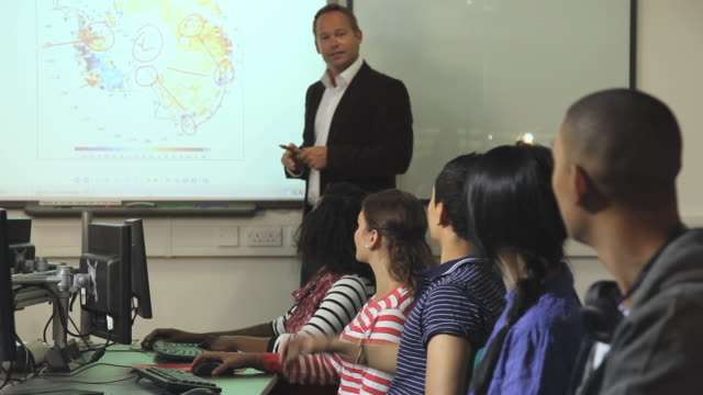 MS Students listening to teacher talking and pointing at map in classroom / London, England