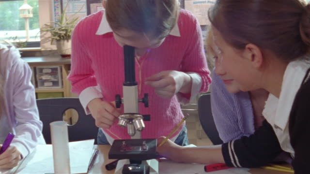 students looking through microscope in science class / pan to teacher assisting student focus microscope / gorham, maine - schoolboy stock videos and b-roll footage