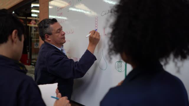 vídeos y material grabado en eventos de stock de los estudiantes prestan atención mientras que el maestro explica algo en la pizarra blanca mientras que otros estudiantes trabajan en su proyecto durante un taller de madera - explicar