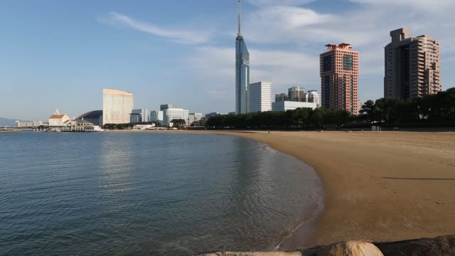 vídeos y material grabado en eventos de stock de students play with a soccer ball on the beach in the momochi seaside park waterfront area as the fukuoka tower, background center, stands in fukuoka,... - vista general