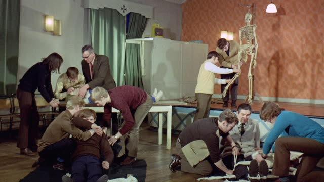 1971 montage students practicing first aid skills / united kingdom - 1971 stock-videos und b-roll-filmmaterial