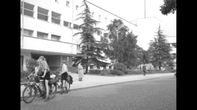students riding down street in front of large building / students riding bikes stop in front of large building / two shots of two students in... - westberlin stock-videos und b-roll-filmmaterial