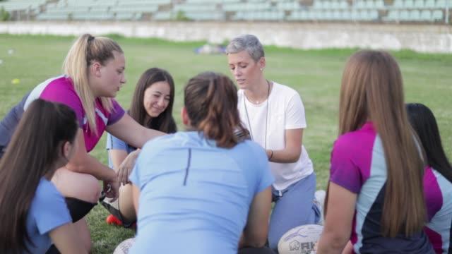 vídeos de stock e filmes b-roll de student's rugby team making play plans with coach - râguebi desporto