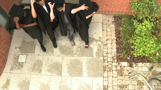 SLO MO MS HA Students running out of university door, throwing mortar boards in the air  / London, England