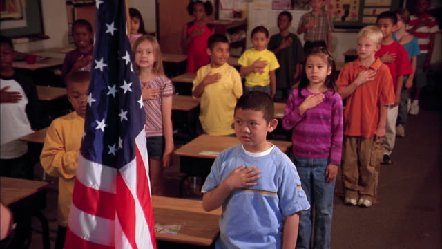 Students say the Pledge of Allegiance in a classroom.