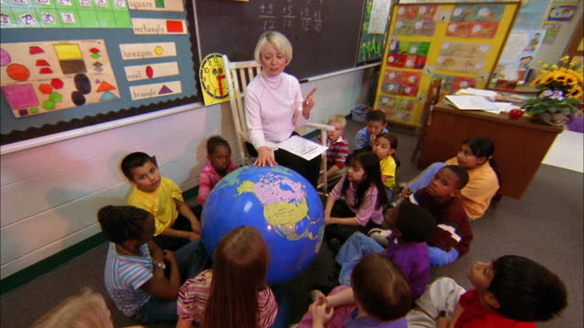Students sit around a large globe while their teacher points out countries.