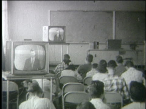B/W 1950 REAR VIEW PAN students sitting at desks watching televisions in classroom