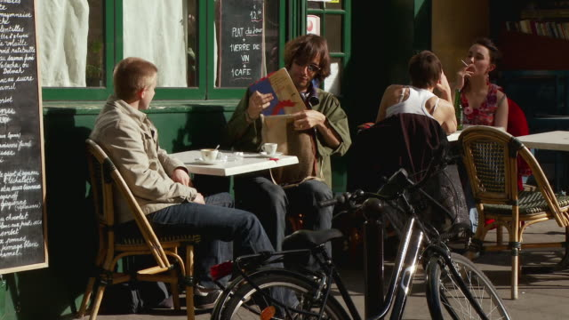 MS TU PAN Students sitting at outdoor cafe table, one getting up on bike and leaving, Rue de la Montagne Saint-Genevieve, Paris, France