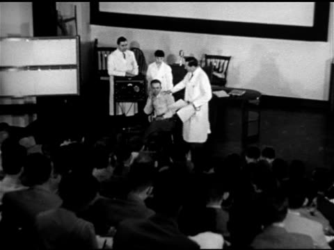 Students sitting in auditorium male sitting on stage w/ three adults in white lab coats standing possibly case study lecture MS Doctor talking seated...