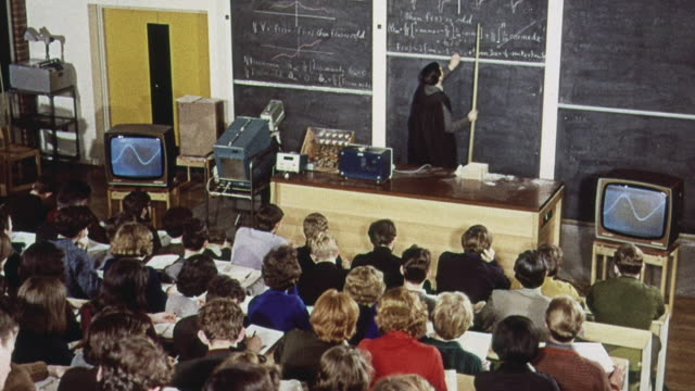vídeos de stock, filmes e b-roll de 1965 montage students taking notes at a lecture while a teacher is standing at a blackboard and another is demonstrating / brighton, england, united kingdom - 1965
