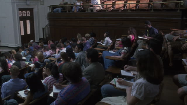 vidéos et rushes de students taking notes while attending a lecture. - professor