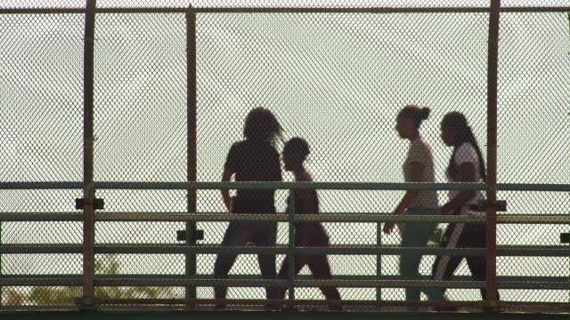 Students travel across a pedestrian roadway bridge on the East Side of Manhattan.