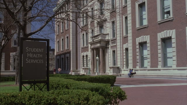 students walk by the student health services building and sign in this establishing shot. - ivy league university stock videos and b-roll footage