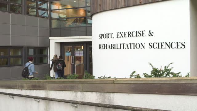 Students walk into and out of the Sport, Exercise and Rehabilitation Sciences building at the University of Birmingham, UK.
