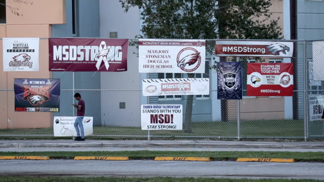 students walk past the building where a mass shooting took place at marjory stoneman douglas high school as they arrive for school on february 14,... - gedenkveranstaltung stock-videos und b-roll-filmmaterial