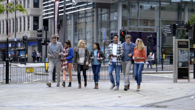 students walking around town using technology - university stock videos and b-roll footage
