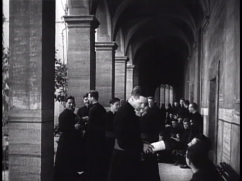 students walking breezeway interior hallway into dining room all dressed in long priest robes talking socializing seminary formation study of... - priest stock videos and b-roll footage