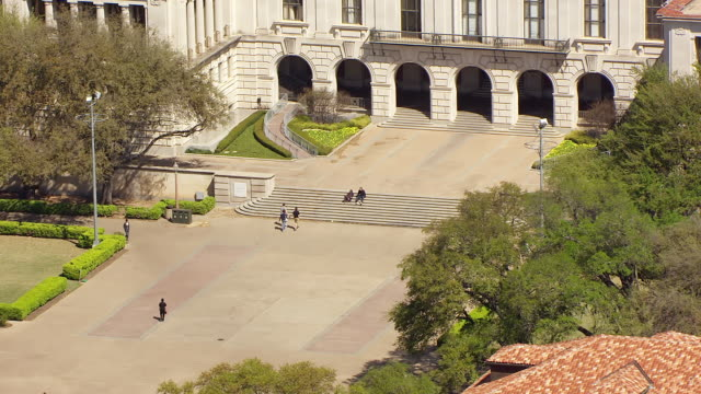 vidéos et rushes de ms aerial tu zi students walking on campus and university of texas tower / austin, texas, united states - texas