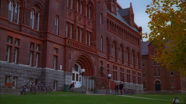 Students walking past red brick campus building, University of Vermont Available in HD.