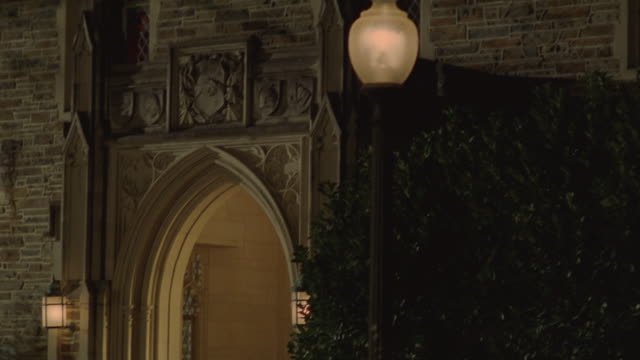 students walking through an archway into a dormitory building at duke university. - arch architectural feature stock videos and b-roll footage