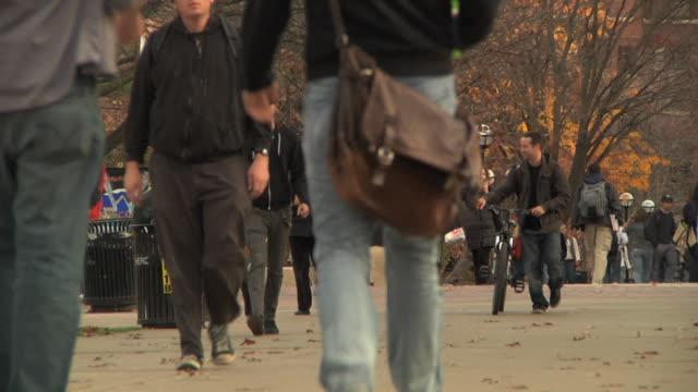 vídeos y material grabado en eventos de stock de slo mo ws students walking through park at university of michigan campus including jogger and bicyclist / ann arbor, michigan, usa - ann arbor