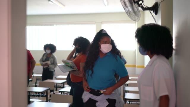 vidéos et rushes de étudiants utilisant le masque de visage quittant la salle de classe - la fin