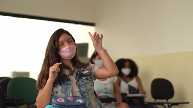 vídeos de stock, filmes e b-roll de alunos usando máscara facial estudando durante a aula na escola - de braço levantado