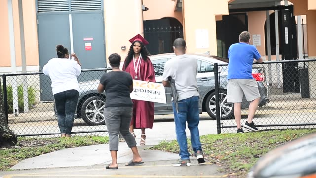 vídeos y material grabado en eventos de stock de students wearing mask waited six feet apart to take part during a graduation ceremony at pembroke pines charter high school on may 15, 2020 in... - pembroke
