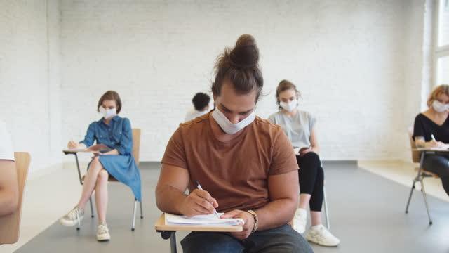 studenten tragen schützende gesichtsmaske bei der vorlesung - schulische prüfung stock-videos und b-roll-filmmaterial