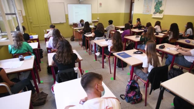 students wearing protective masks sit inside a school classroom with separate desks for social distancing measures to prevent covid 19 on liceo... - learning stock videos & royalty-free footage