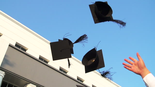 Students with congratulations throwing graduation hats in the air celebrating.