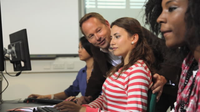MS ZI Students working in computer class, teaches talking with female student / London, England